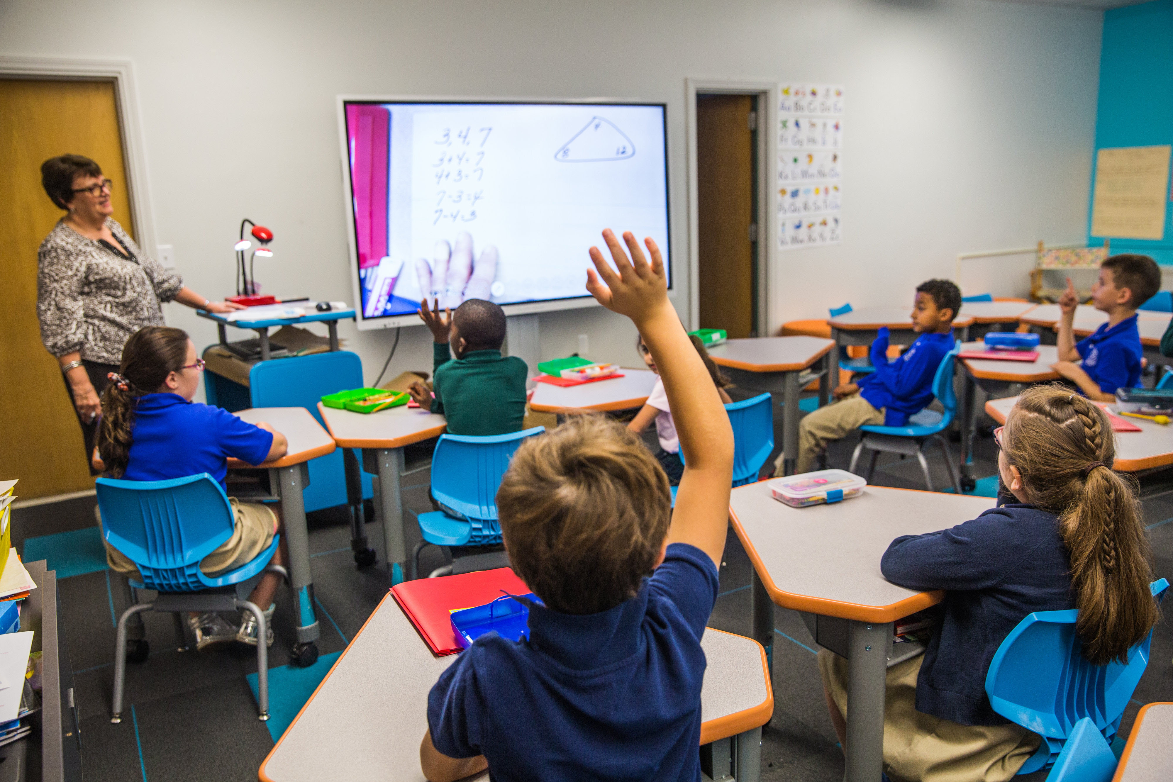 Students at desk; boy with raised hand